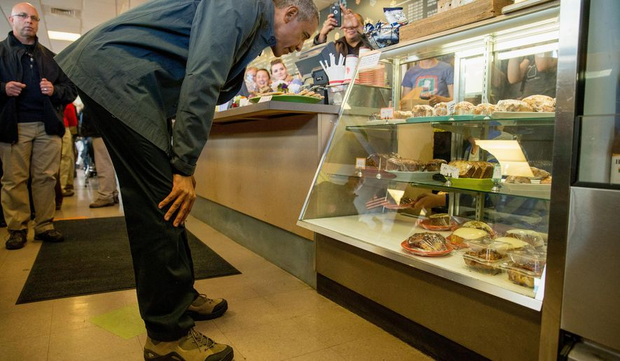 President Barack Obama looks at a pastry display during a stop at at Snow City Cafe in Anchorage, Alaska, Tuesday, Sept. 1, 2015. Obama is on a historic three-day trip to Alaska aimed at showing solidarity with a state often overlooked by Washington, while using its glorious but changing landscape as an urgent call to action on climate change. (AP Photo/Andrew Harnik)