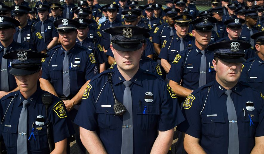 Law enforcement personnel stand row by row outside of Fenton High School, Tuesday, Sept. 1, 2015, for the funeral of Michigan State Police trooper Chad Wolf in Fenton, Mich. The 38-year-old Wolf died Friday, hours after he was struck by a car hauling a trailer and dragged for miles in northern Oakland County. He had been a trooper since 2008. (Jake May/The Flint Journal-MLive.com via AP) LOCAL TELEVISION OUT; LOCAL INTERNET OUT; MANDATORY CREDIT