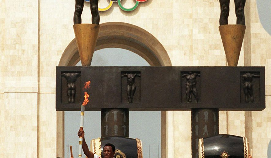 FILE - In this April 27, 1996, file photo, Olympic decathlon champion Rafer Johnson, who was the last person to carry the torch on its international journey to the 1984 Summer Olympics in Los Angeles, displays the torch with the Olympic flame after its arrival at the Los Angeles Memorial Coliseum in Los Angeles. The U.S. Olympic Committee on Tuesday, Sept. 1, 2015,  named Los Angeles as its candidate for the 2024 Games, replacing Boston's soured bid and marking a comeback for LA's dream of becoming a three-time host of the global sports competition.  (AP Photo/Reed Saxon, File)