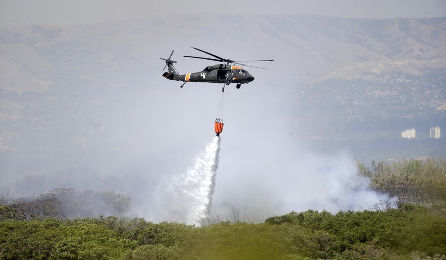 A helicopter dumps water on a brush fire, Tuesday, Sept. 1, 2015, roughly 15 miles from Salt Lake City. A brush fire fueled by shifting winds near the mouth of a Salt Lake City-area canyon burned an outbuilding Tuesday as authorities went door-to-door in a nearby subdivision and recommended evacuations for at least 30 homes. The homes were in a neighborhood north of the fire, which was burning in a field near a ravine at the mouth of Little Cottonwood Canyon. (AP Photo/Rick Bowmer)