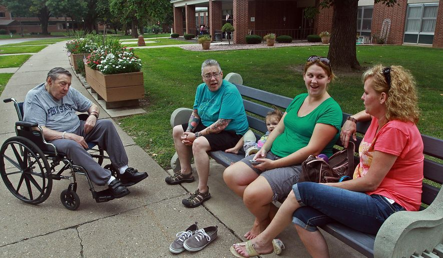 In this Saturday Aug. 29, 2015 photo, Illinois Veterans Home resident Godfrey Rezba, left, visits with family members out front of Elmore Infirmary in Quincy, Ill. The death toll from a Legionnaires' disease outbreak at the western Illinois veterans home climbed to seven Tuesday, Sept. 1, 2015, with the state's public health director suggesting more fatalities are likely. Officials with the Illinois Department of Veterans Affairs and the state Department of Public Health said that each of the victims at the 129-year-old facility had underlying medical conditions, with an average age of 86. (Michael Kipley/The Quincy Herald-Whig via AP)