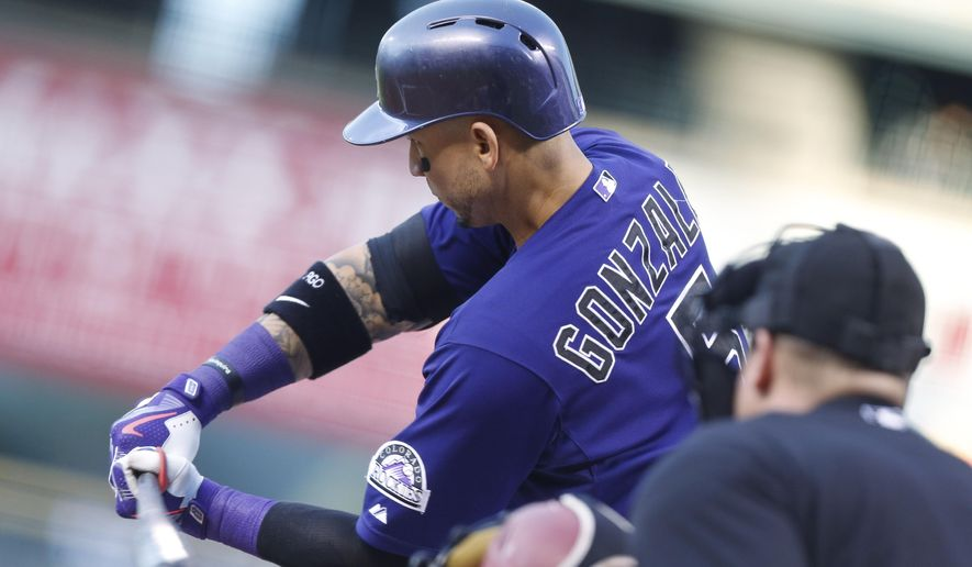 Colorado Rockies' Carlos Gonzalez strikes out on a pitch from Arizona Diamondbacks starting pitcher Robbie Ray to end the first inning of a baseball game Monday, Aug. 31, 2015, in Denver. (AP Photo/David Zalubowski)