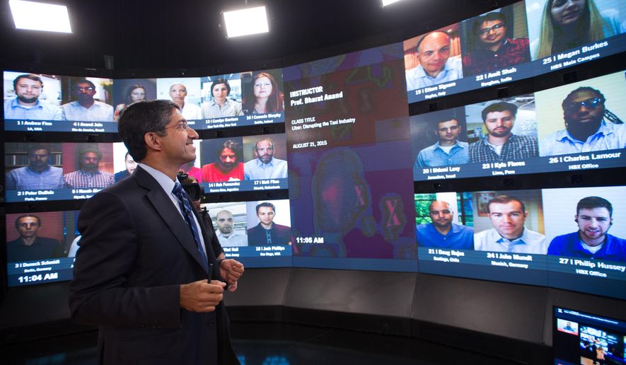 Harvard Business School Professor and faculty chair of HBX Bharat Anand demonstrates HBX Live, an online classroom that allows real-time interaction between professors and students from around the world, at the WGBH television studios in Boston, Friday, Aug. 21, 2015. (AP Photo/Gretchen Ertl)