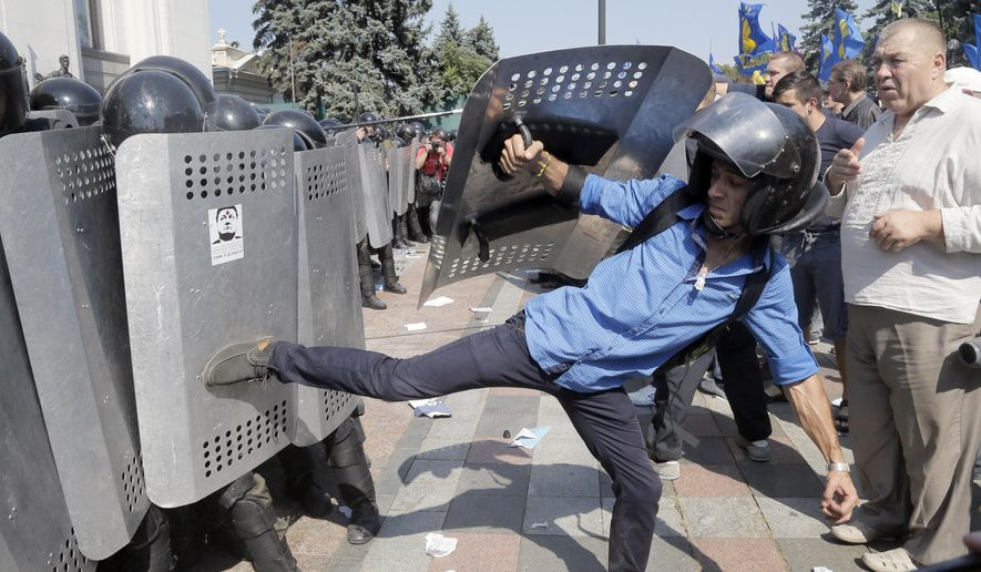 Ukrainian protesters, one using police riot equipment, clash with police after a vote to give greater powers to the east, outside the Parliament, Kiev, Ukraine, Monday, Aug. 31, 2015. The Ukrainian parliament has given preliminary approval to a controversial constitutional amendment that would provide greater powers to separatist regions in the east. Hundreds of people gathered in front of the parliament to protest against the amendment. (AP Photo/Efrem Lukatsky)