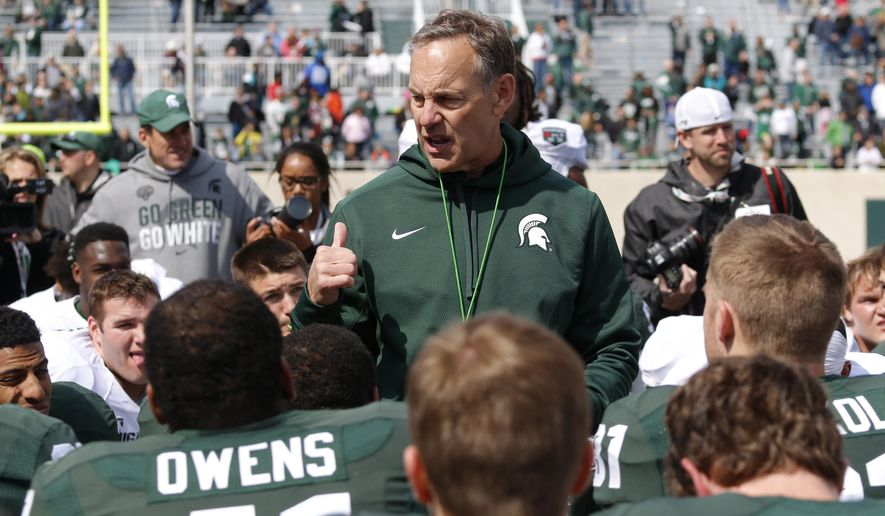 FILE - In this April 25, 2015, file photo, Michigan State coach Mark Dantonio, center, talks to his players following an NCAA college football scrimmage in East Lansing, Mich. Dantonio's toughest job this week might be making sure No. 5 Michigan State is focused on opening with a win Friday night at Western Michigan, and not looking ahead to next week's matchup against No. 7 Oregon. (AP Photo/Al Goldis, File)