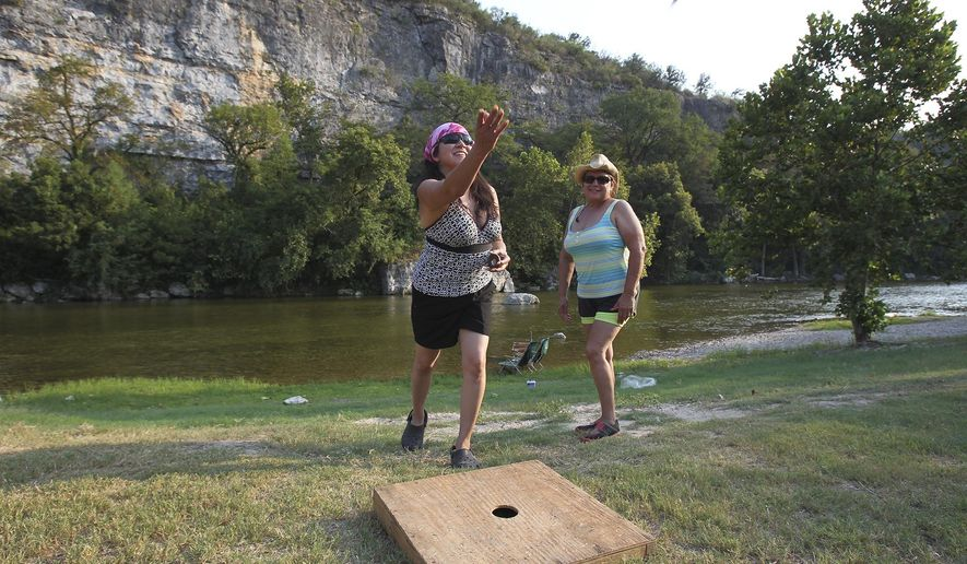 Elizabeth Villarreal throws as  Becky Velasquez watches during a game of washers at the KL Ranch Camp in New Braunfels, Texas on Aug. 28, 2015. A new flood alert system, using solar-powered gauges and sirens, has been installed along the Guadalupe River in Comal County upstream from New Braunfels. The $308,000 project, tentatively set for dedication Sept. 10, was underwritten by Comal and Guadalupe counties, the city of New Braunfels and a local recreation district. (Tom Reel/The San Antonio Express-News via AP) RUMBO DE SAN ANTONIO OUT; NO SALES; MANDATORY CREDIT