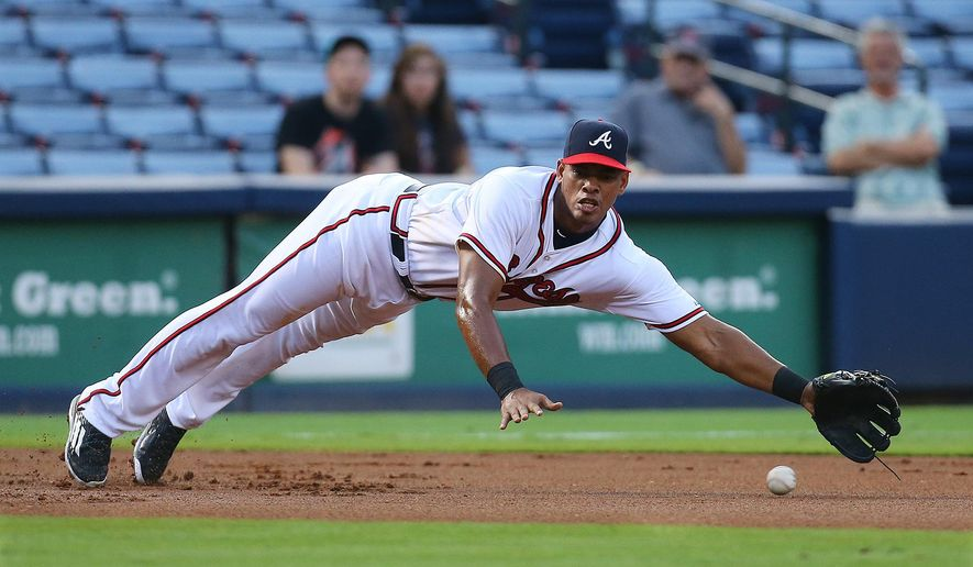 Atlanta Braves new third baseman Hector Olivera dives just missing a single by Miami Marlins Martin Prado during the first inning of a baseball game, Tuesday, Sept. 1, 2015 in Atlanta. Cuban defector Hector Olivera was called up for Tuesday's game against the Miami Marlins, looking to show he was worth the steep price the Braves paid to land him just before the deadline for non-waiver trades. (Curtis Compton/Atlanta Journal-Constitution via AP)  MARIETTA DAILY OUT; GWINNETT DAILY POST OUT; LOCAL TELEVISION OUT; WXIA-TV OUT; WGCL-TV OUT; MANDATORY CREDIT