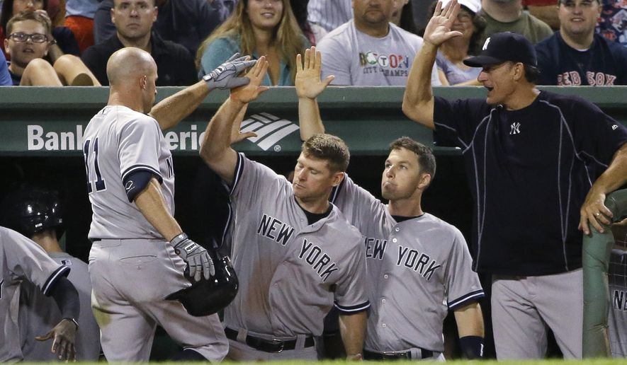 New York Yankees' Brett Gardner, left, is welcomed into the dugout after hitting a home run during the eighth inning of a baseball game against the Boston Red Sox, Tuesday, Sept. 1, 2015, at Fenway Park, in Boston. The Yankees won 3-1. (AP Photo/Steven Senne)
