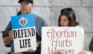 Ralliers at the Utah Capitol in Salt Lake City stood in support of Gov. Gary Herbert's decision to remove the state from federal funding of Planned Parenthood. The latest undercover video implies the organization broke several laws in its fetal tissue business. (Associated Press) ** FILE **