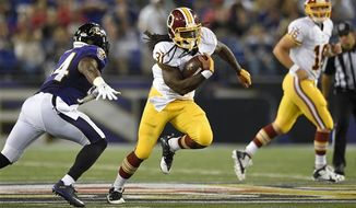 Washington Redskins running back Matt Jones, center, rushes past Baltimore Ravens linebacker Zach Orr, left, in the second half of a preseason NFL football game, Saturday, Aug. 29, 2015, in Baltimore. (AP Photo/Nick Wass)
