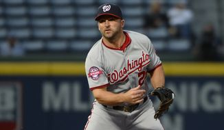 Washington Nationals second baseman Dan Uggla (26) turns a double play to force out Atlanta Braves' Nick Markakis (22) during the third inning inning of a baseball game Wednesday, April 29, 2015, in Atlanta. (AP Photo/David Tulis)