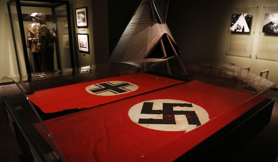 Two flags are on display in an exhibit about the Comanche Code Talkers at the Comanche National Museum & Cultural Center in Lawton, Okla, Thursday, Sept. 26, 2013.  At left is the Baltic Cross captured by Comanche Code Talker Larry Saupitty, at right is a Nazi German flag with the swastika captured by Code Talker Charles Chibitty. (AP Photo/Sue Ogrocki) **FILE**