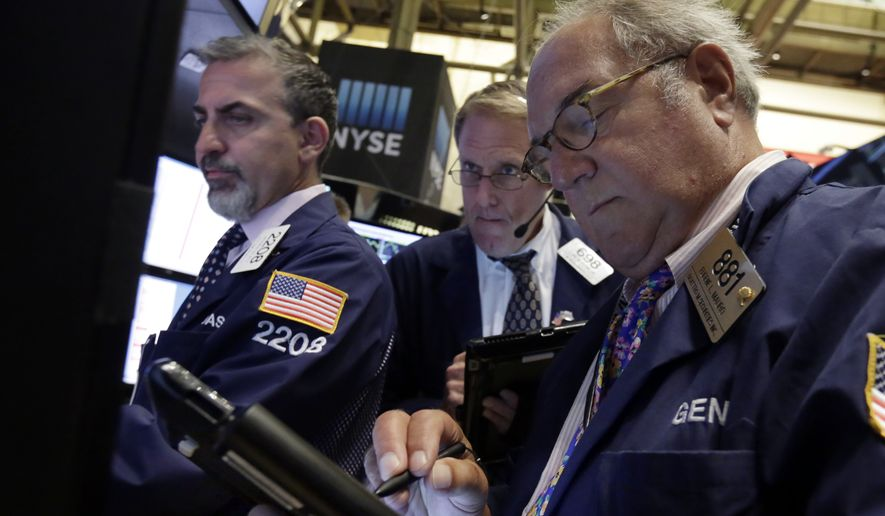 Trader Eugene Mauro (right) works on the floor of the New York Stock Exchange on Sept. 1, 2015. (Associated Press)