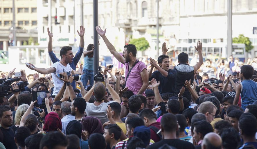 Migrants demonstrate  in front of the Keleti Railway Station in Budapest, Hungary, Tuesday, Sept.  1, 2015, after the police stopped them from getting on a train to Germany and evacuated the station. (Zoltan Balogh/MTI via AP)