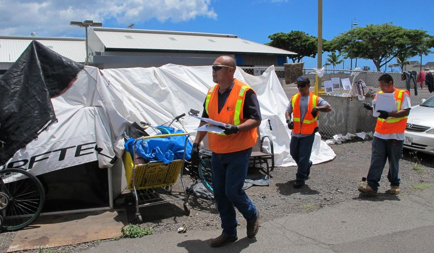 Honolulu Department of Facility Maintenance crews post signs at the Kakaako homeless encampment in Honolulu on Tuesday, Sept. 1, 2015. The signs posted on the outer streets of the Kakaako encampment say authorities will enforce rules next week that prohibit leaving personal property on sidewalks. (AP Photo/Cathy Bussewitz)