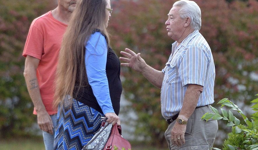 Rowan County Clerk Kim Davis, foreground left, is greeted as she arrives for work at the Rowan County Courthouse in Morehead, Ky., Tuesday, Sept. 1, 2015. Davis' appeal to the U.S. Supreme Court was turned down on Monday, and now she is under federal orders to begin issuing marriage licenses. (AP Photo/Timothy D. Easley)