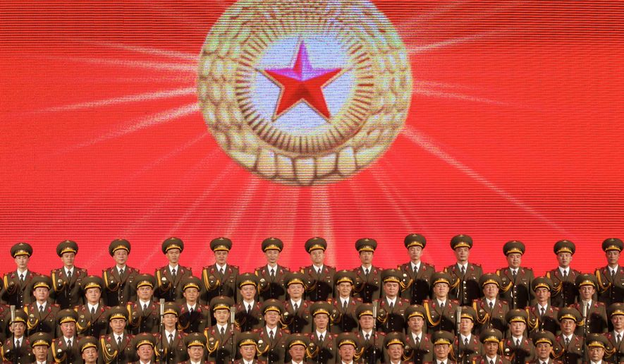In this photo taken Monday, Aug. 31, 2015, the North Korean male choir performs at the Tchaikovsky Concert Hall in Moscow, Russia. The North Korean National Choir has performed for the first time in the Russian capital, putting on a military-inspired concert, with members of the male choir wearing full military dress. As they sang, a giant screen behind the stage showed scenes of military parades, air shows and North Korea's authoritarian leader, Kim Jong Un. North Korea's ambassador to Russia said Monday evening's concert was part of a new cultural exchange between the two countries. (AP Photo/Pavel Golovkin)