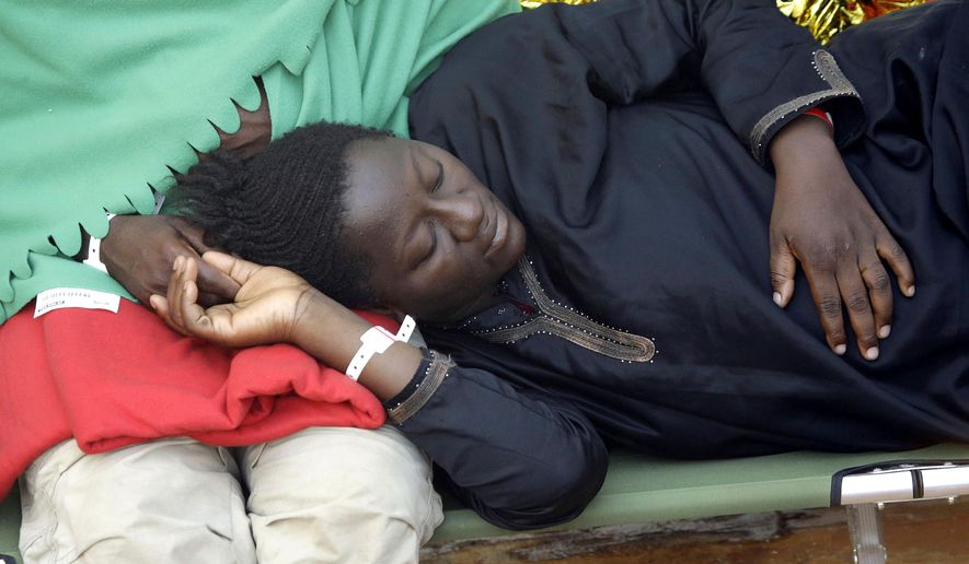 Nine-month pregnant Aisha, from Ghana, holds the hand of her husband as she lies on a stretcher on the bridge of the Norwegian Siem Pilot ship, Wednesday, Sept. 2, 2015. The Siem Pilot is carrying to the Italian Port of Cagliari hundreds of migrants rescued in several operations in the Mediterranean sea. (AP Photo/Gregorio Borgia)