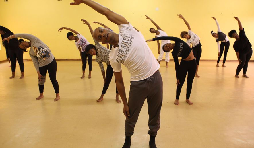 Beginner dancers take part in a master class in Johannesburg's historic Soweto township on Wednesday Sept 2, 2015, given by instructor Vernard J. Gilmore, front, from the Alvin Ailey American Dance Theater a day before they begin the South African leg of their international tour. The dance company last visited South Africa 17-years ago, soon after the end of apartheid, and several South Africans have won scholarships to the Ailey school in the United States. (AP Photo/Denis Farrell)