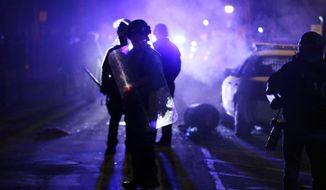 FILE - In this Nov. 25, 2014 file photo, police officers watch protesters as smoke fills the streets in Ferguson, Mo. after a grand jury's decision in the fatal shooting of Michael Brown. A final Justice Department report which will be released Thursday and obtained in advance by The Associated Press warns similar problems could happen in other places roiled by mistrust between law enforcement and the community. (AP Photo/Charlie Riedel, File)