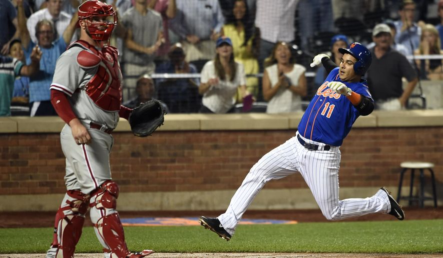 New York Mets' Ruben Tejada (11) slides into home plate past Philadelphia Phillies catcher Cameron Rupp for an inside the park two-run home run in the second inning of a baseball game on Wednesday, Sept. 2, 2015, in New York. (AP Photo/Kathy Kmonicek)