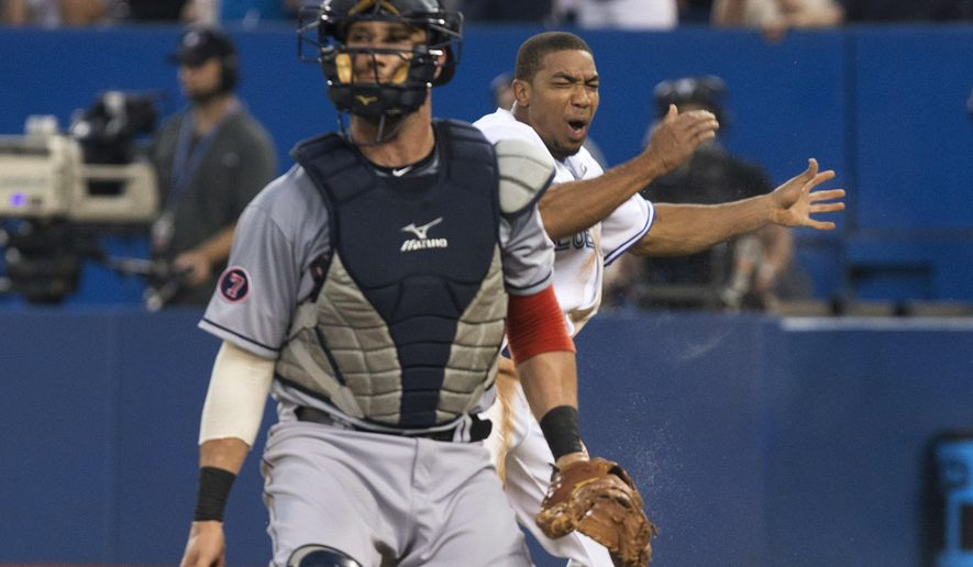 Toronto Blue Jays' Ben Revere, right, celebrates behind Cleveland Indians catcher Yan Gomes after sliding into home plate to score on a Josh Donaldson double during the second inning of a baseball game Wednesday, Sept. 2, 2015, in Toronto. (Chris Young/The Canadian Press via AP)