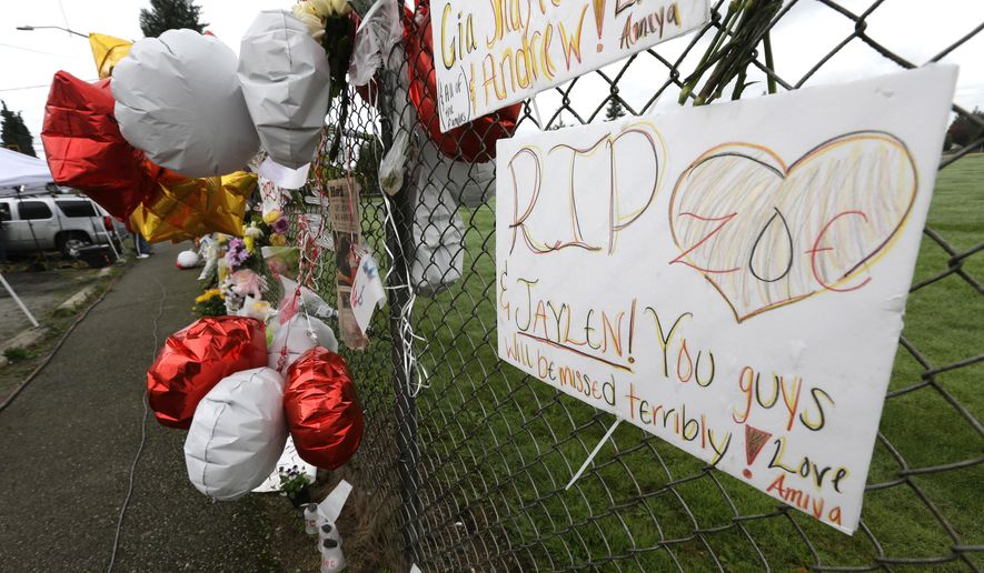 FILE - In this Oct. 27, 2014 file photo, a hand-written sign is attached to a fence at a growing memorial at Marysville Pilchuck High School in Marysville, Wash. The sign makes reference to Jaylen Fryberg, a freshman at the school who fatally shot four friends in the school cafeteria on Oct. 24, 2014 before killing himself. A report released Tuesday, Sept. 1, 2015 said that Fryberg's motive remains unclear, but that he sent a group text message to his family outlining his funeral wishes and apologizing to the parents of the teenagers he was about to kill. (AP Photo/Ted S. Warren, file)