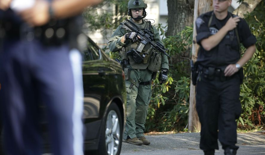 Law enforcement officials stand near an entrance to a street Wednesday, Sept. 2, 2015, where police say multiple shots were fired into a Millis Police cruiser, in Millis, Mass. Police say the cruiser then crashed into a tree and caught on fire. Police from several local towns were helping state police investigate what happened and searching for the suspect. No injuries were immediately reported. (AP Photo/Steven Senne)