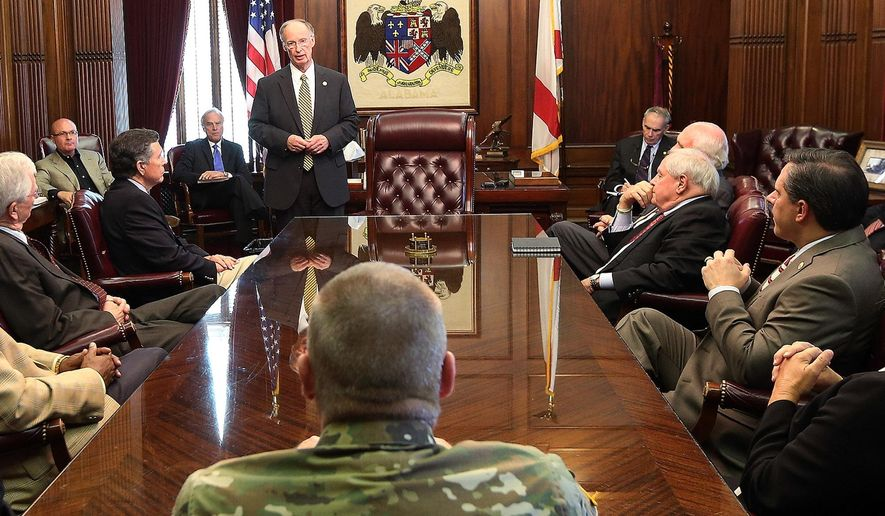 In this Monday, Aug. 31, 2015, photo provided by  Alabama Governor's Office, Alabama Gov. Robert Bentley, center back, meets with cabinet members in Montgomery, Ala. A judge ordered Gov. Bentley's divorce case to be sealed from public view Monday, Aug. 31, 2015, and the governor told cabinet members that he would not let distractions get in the way of his push for budget and policy changes. (Jamie Martin/Alabama Governor's Office via AP)