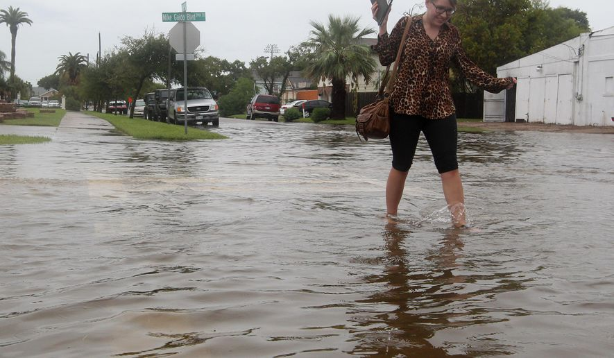 Elisa Combs, a student at Galveston College, wades across 39th Street in Galveston, Texas on Tuesday, Sept. 1, 2015. Heavy rains on Tuesday flooded streets across the island.(Jennifer Reynolds/The Galveston County Daily News via AP)