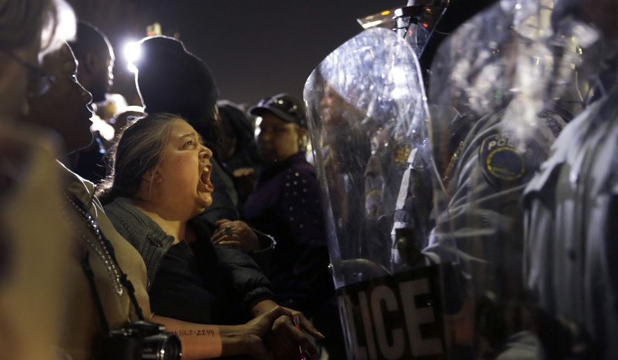 A protester yells at police outside the Ferguson, Mo., Police Department on Aug. 11, 2014, during a demonstration sparked by the fatal shooting of Michael Brown. (Associated Press) **FILE**