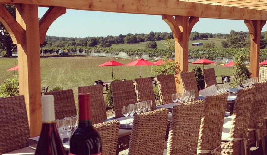 """This undated photo provided by Visit Loudoun shows wine bottles on the patio at Greenhill Winery in Middleburg, Va., one of two dozen wineries in Loudoun County. Located about an hour's drive from  Washington, D.C., the area calls itself """"DC's Wine Country."""" (Visit Loudoun via AP)"""
