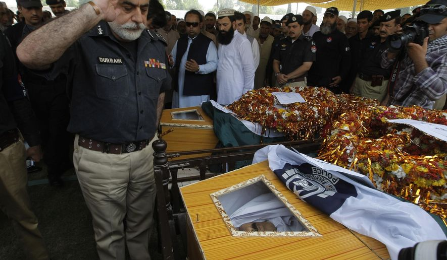 Police chief Nasir Khan Durrani salutes to police officers killed in an attack in Peshawar, Pakistan, Wednesday, Sept. 2, 2015. Three policemen were killed and six others injured when armed gunmen ambushed a raiding police party during a search operation in Urmar Payan area of the provincial capital, official said. (AP Photo/Mohammad Sajjad)