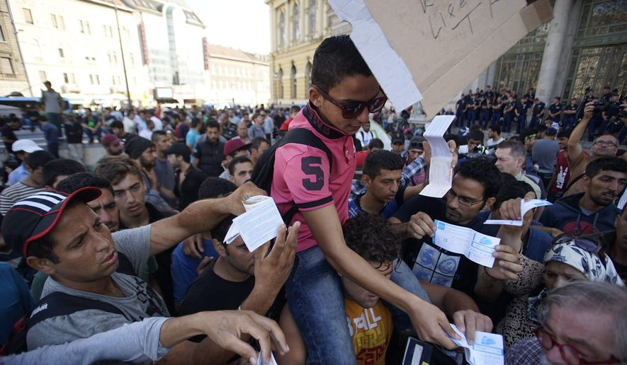 Migrants hold up their train tickets outside the Keleti Railway Station in Budapest, Hungary, Wednesday, Sept. 2, 2015. (Zoltan Balogh/MTI via AP)