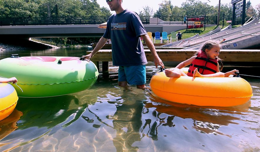 In an Aug. 27, 2015 photo, Andy Raymond, left of Eaton Rapids, Mich., gets ready to tube on the Platte River with Macy Gruesbeck, 6, and other family members at Riverside Canoe Trips near Honor. Riverside's 70 employees wrangle 150 canoes and 200 kayaks each summer. (Jan-Michael Stump/Traverse City Record-Eagle via AP) MANDATORY CREDIT