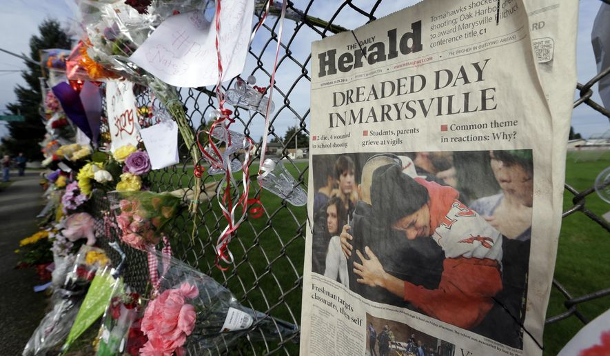 """FILE - In this photo taken Oct. 27, 2014, an edition of The Daily Herald from Everett, Wash. with the headline """"Dreaded Day in Marysville"""" is shown as part of a growing memorial on a fence around Marysville Pilchuck High School in Marysville, Wash. Jaylen Fryberg, a freshman at the school, fatally shot four friends in the school cafeteria on Oct. 24, 2014 before killing himself. A report released Tuesday, Sept. 1, 2015 said that Fryberg's motive remains unclear, but that he sent a group text message to his family outlining his funeral wishes and apologizing to the parents of the teenagers he was about to kill. (AP Photo/Ted S. Warren, file)"""