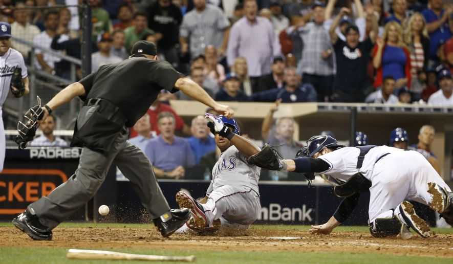 Texas Rangers' Adrian Beltre scores as San Diego Padres catcher Derek Norris loses the ball, while umpire Mark Carlson moves in to make the call during the seventh inning of a baseball game Tuesday, Sept. 1, 2015, in San Diego. (AP Photo/Lenny Ignelzi)