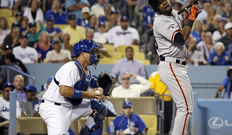 San Francisco Giants' Alejandro De Aza, right, reacts after striking out as Los Angeles Dodgers catcher A.J. Ellis starts to stand during the seventh inning of a baseball game in Los Angeles, Tuesday, Sept. 1, 2015. (AP Photo/Chris Carlson)