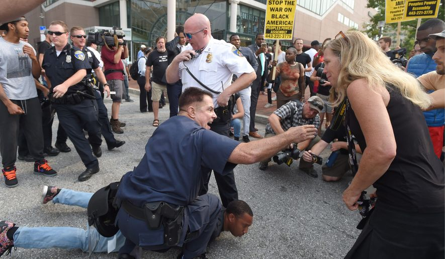 Baltimore Police try to control protesters while detaining activist Kwame Rose. Demonstrators marched to Pratt Street and the Inner Harbor on Wednesday during the first court hearing in the case of six police officers criminally charged in the death of Freddie Gray. Six Baltimore police officers face charges. (The Baltimore Sun via Associated Press)