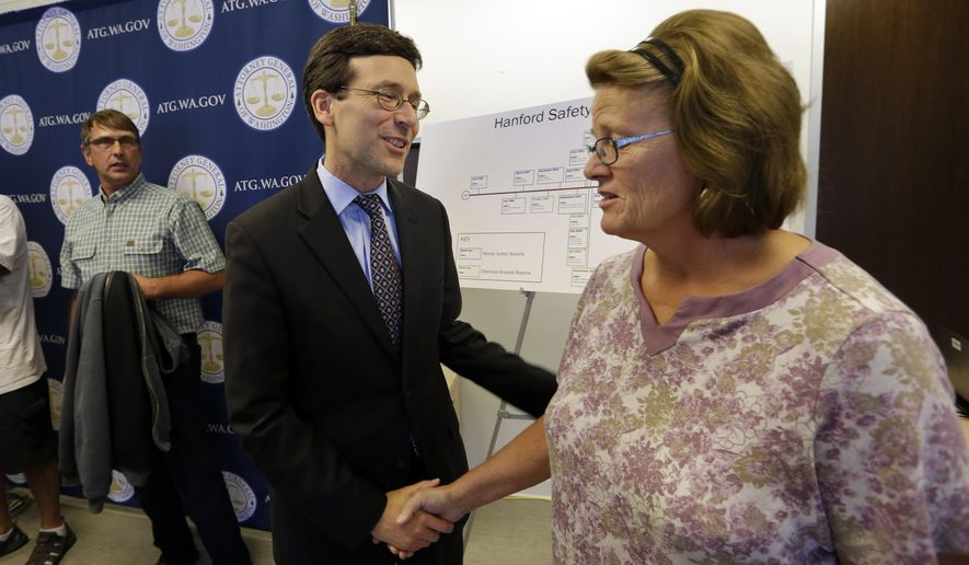 Washington Attorney General Bob Ferguson, center, thanks Diana Gregg, of Kennewick, Wash., following a news conference, Wednesday, Sept. 2, 2015, in Seattle. Gregg was injured in a vapor release at the Hanford Nuclear Reservation in 2007. Ferguson announced the filing of a lawsuit by his office against the U.S. Department of Energy and its contractor, Washington River Protection Solutions, alleging that hazardous tank vapors at Hanford pose serious risk to workers there. In June, Ferguson said he would oppose a U.S. Department of Energy request to have more time to empty the next group of waste storage tanks at Hanford. (AP Photo/Elaine Thompson)