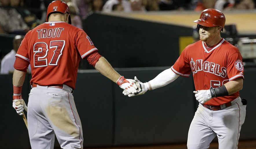 Los Angeles Angels' Kole Calhoun, right, is congratulated by Mike Trout after hitting a solo home run off Oakland Athletics pitcher Dan Otero during the seventh inning of a baseball game in Oakland, Calif., Tuesday, Sept. 1, 2015. (AP Photo/Jeff Chiu)