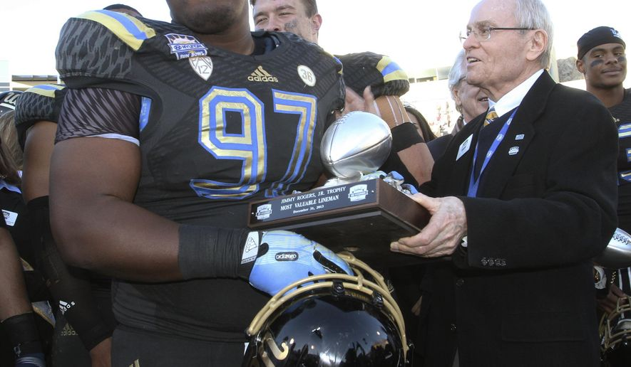 FILE - In this Dec. 31, 2013, file photo, UCLA's Kenny Clark is presented the Most Valuable Lineman trophy after UCLA defeated Virginia Tech 42-12 in an NCAA college football game in El Paso, Texas. Clark, a run-stuffing defensive tackle, has evolved into one of the best overall players in the Pac-12. (AP Photo/Victor Calzada, file)