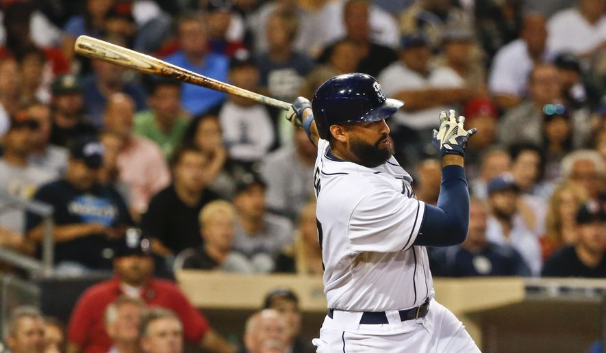 San Diego Padres' Matt Kemp follows through on a two-run double against the Texas Rangers during the third inning of a baseball game Tuesday, Sept. 1, 2015, in San Diego. (AP Photo/Lenny Ignelzi)
