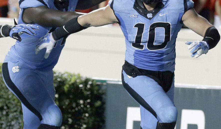 FILE - In this Aug. 30, 2014 file photo, North Carolina's Shakeel Rashad and Jeff Schoettmer (10) celebrate Schoettmer's interception and touchdown against Liberty during the second half of an NCAA college football game in Chapel Hill, N.C. North Carolina has overhauled its defensive coaching staff and scheme after giving up the most programs and yards in program history last year. (AP Photo/Gerry Broome, File)