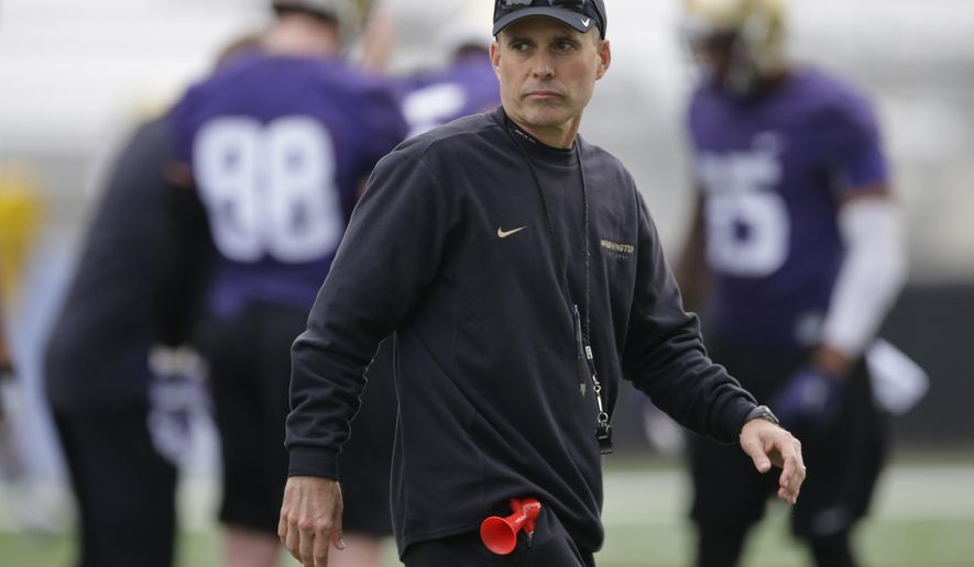 FILE - In this March 30, 2015, file photo, Washington coach Chris Petersen watches NCAA college football practice in Seattle. Washington plays Idaho, a team Petersen formerly coached, on Friday, Sept. 4. (AP Photo/Ted S. Warren, File)
