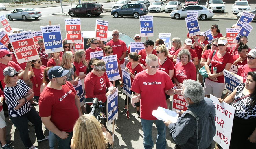 Greg Olson, (wearing glasses) president of the Pasco Association of Educators, is surrounded by  picketing teacher union members on Tuesday, Sept. 1, 2015 as reporters seek his response to the Pasco School District seeking legal action against the striking union. (Bob Brawdy/Tri-City Herald via AP)