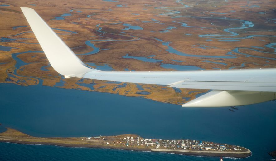 Air Force One, carrying President Barack Obama, flies over the island village of Kivalina, an Alaska Native community of 400 people already receding into the ocean as a result of rising sea levels, on its way to Ralph Wien Memorial Airport, Wednesday, Sept. 2, 2015, in Kotzebue, Alaska. Residents of the Native village threatened by erosion were thankful Wednesday for President Barack Obama's attention to their plight, saying they hope his visit to Alaska will help them secure funding to build a critical evacuation road to drier ground. (AP Photo/Andrew Harnik)