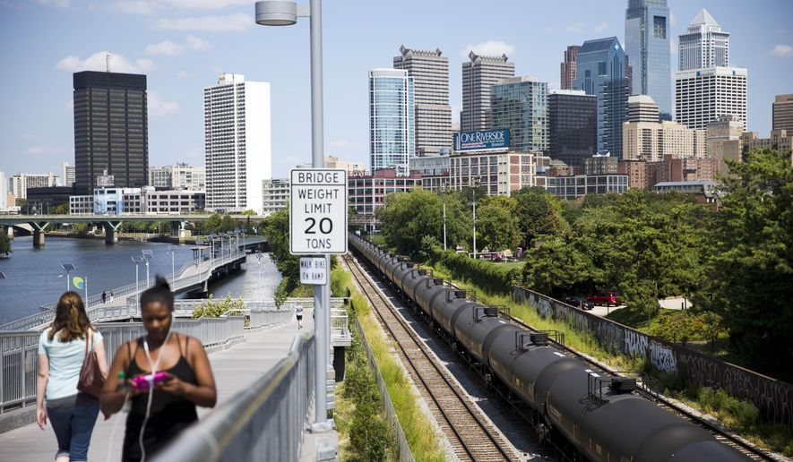 Pedestrians walk past train tank cars with signs indicating  petroleum crude oil standing idle on the tracks in Philadelphia on Wednesday, Aug. 26, 2015. While railroads have long carried hazardous materials through congested urban areas, cities are now scrambling to formulate emergency plans and to train firefighters amid the latest safety threat: a fiftyfold increase in crude shipments that critics say has put millions of people living or working near the tracks at heightened risk of derailment, fire and explosion. (AP Photo/Matt Rourke)