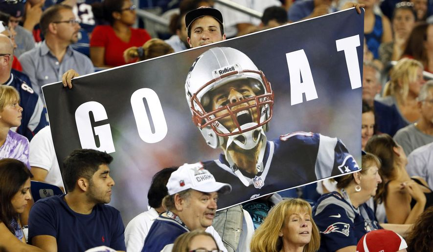 Fans hold a photo of New England Patriots quarterback Tom Brady in the first half of an NFL football game Thursday, Sept. 3, 2015, in Foxborough, Mass. Federal Judge Richard M. Berman overturned NFL Commissioner Roger Goodell's four-game suspension of New England quarterback Tom Brady Thursday morning. The league said it will appeal the ruling. (AP Photo/Winslow Townson)
