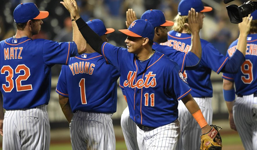 New York Mets shortstop Ruben Tejada (11) celebrates the Mets' 9-4 win over the Philadelphia Phillies in a baseball game Wednesday, Sept. 2, 2015, in New York. Tejada had four RBIs during the game, including an inside-the-park home run. (AP Photo/Kathy Kmonicek)